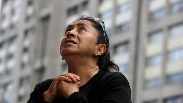 A woman prays during a mass held outside Saint James Apostle Parish because the church building suffered some damage during the Mexico City earthquake. As the search continues for survivors and bodies, officials are inspecting buildings to determine which are unsafe.