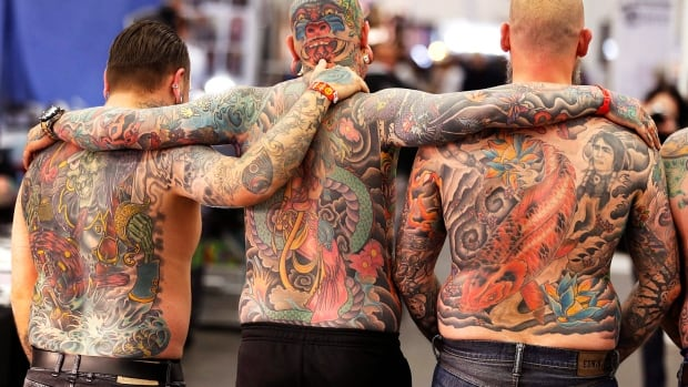Three men show the tattoos on their backs on the first day of the Frankfurt Tattoo Convention on April 21, 2017. University of Ottawa researchers are now studying whether heavy tattooing could interfere with the body's ability to regulate its temperature.