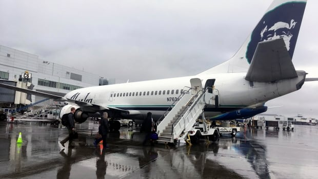 Passengers board an Alaska Airlines jet from the rear using stairs at Ted Stevens Anchorage International Airport in Anchorage. The airline is retiring its combi planes, Boeing 737-400s designed to be half cargo immediately behind the cockpit and then seating for 72 passengers in the rear.