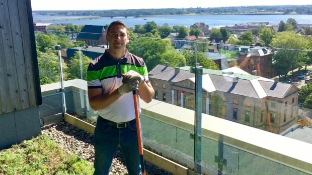Shaman Ferraro takes a break from raking the meadow on the 11th storey of the Holman Grand Hotel in Charlottetown.