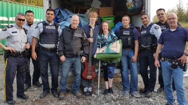 Newlyweds Nathan Drover and Sabrina Perry-Drover pose with police and some of their recovered possessions. The couple's U-Haul was stolen from an Abbotsford parking lot almost two weeks ago.