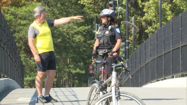 Claude Beaulé and a bike patrol officer discuss the details of the incident in which he ran into nylon wire strung across the Claude-Brunet Bridge in the Southwest borough.