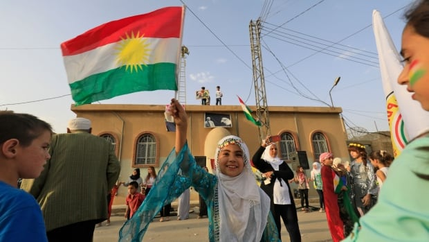 A Syrian Kurdish girl waves a Kurdish flag in the northeastern Syrian city of Qamishli in support of the independence referendum in Iraq's autonomous northern Kurdish region. The vote is likely to be a resounding Yes when official results are revealed later this week.