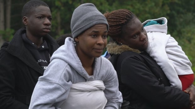 Lillian, centre, who has her 22-month-old son strapped to her back, pauses before she illegally crosses into Canada from upstate New York.