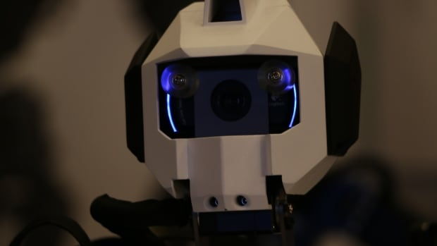 A robot on display at The Intelligent Robots and Systems Conference turns its head and films passersby through camera's installed in its eyes.