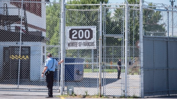 A guard stands outside the gates of an immigrant holding centre in Laval, Que. Immigration holding facilities in Vancouver and Laval will be replaced as part of a $138-million overhaul intended to improve detention conditions for newcomers to Canada.