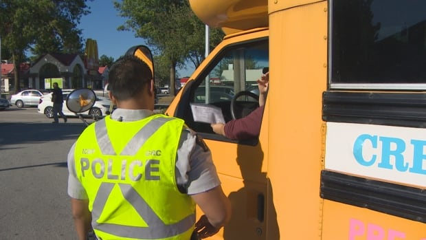 The bus driver for a Surrey day care hands over her insurance information to an RCMP officer before being ticketed for using an electronic device while driving on Wednesday, Sept. 27, 2017.