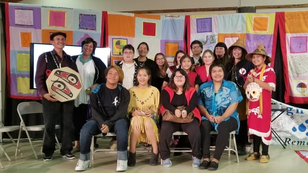 Youth from the 'Na Aksa Gyilak'yoo School near Terrace, B.C., pose for a photo with their principal, cultural adviser and members of the national MMIWG inquiry team, after their performance Wednesday in Smithers, B.C., of a song about the Highway of Tears.