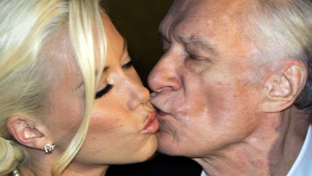 Playboy magazine founder Hugh Hefner kisses then-girlfriend Kendra Wilkinson after their arrival for his 80th birthday party in Munich in 2006.