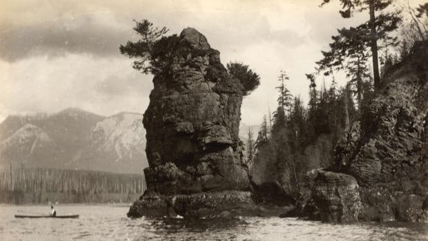 Taken in 1889 or 1890, this photo shows a man in a canoe paddling past Siwash Rock. Traditional Indigenous stories about the rock date back thousands of years.