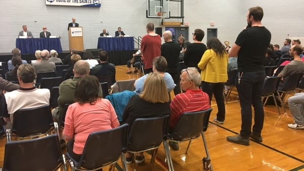 Residents stand in line to ask questions of the four candidates running for council for Ward 6 at a forum Thursday evening at St. Joseph High School.