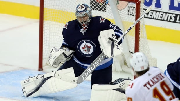 Winnipeg Jets' newcomer Steve Mason (35) makes a blocker save while playing against the Calgary Flames in a pre-season matchup.