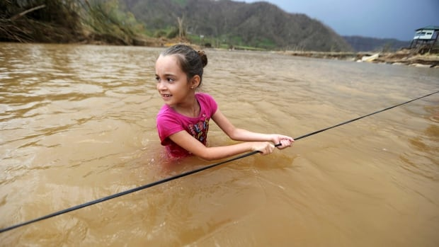 Ruby Rodriguez, 8, wades across the San Lorenzo River with her family after a bridge was swept away by Hurricane Maria, in Morovis, Puerto Rico, on Wednesday. The mayor of the island's capital made an emotional plea for help Friday.
