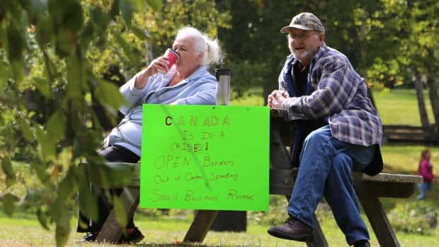 Two of the four Storm Alliance protesters who gathered at Odell Park in Fredericton.