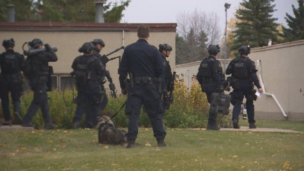 Heavily armed police tactical officers approaching the apartment building afternoon that was home to Abdulahi Hasan Sharif, the man CBC has identified as being the suspect in Saturday's attacks in Edmonton.