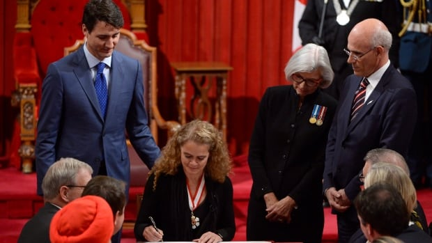 Canada's 29th Governor General, Julie Payette, signs her official instruments as Prime Minister Justin Trudeau and Chief Justice of Canada Beverley McLachlin stand and watch in the Senate chamber during her installation ceremony Monday.