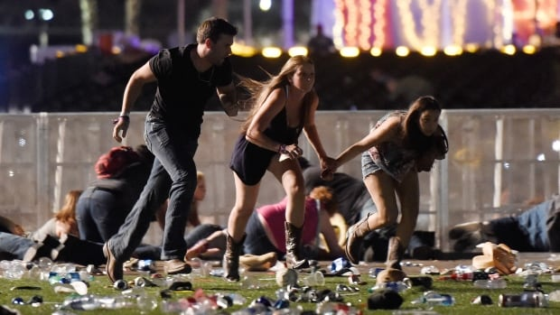 People run from the Route 91 Harvest country music festival after a gunman opened fire on the crowd.
