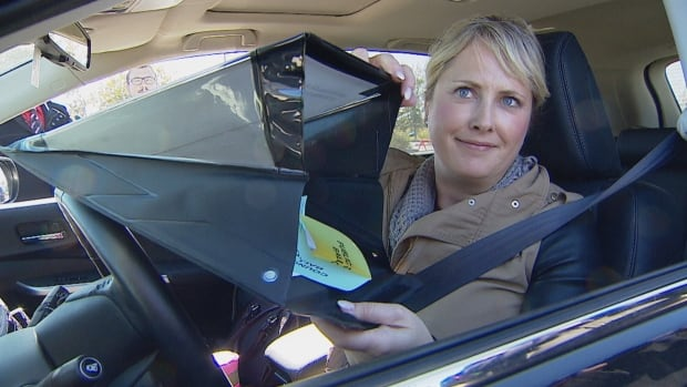 Sheila Johnstone with the City of Calgary shows off one of the mobile privacy folders Calgarians can use to vote in advance without ever leaving their car.