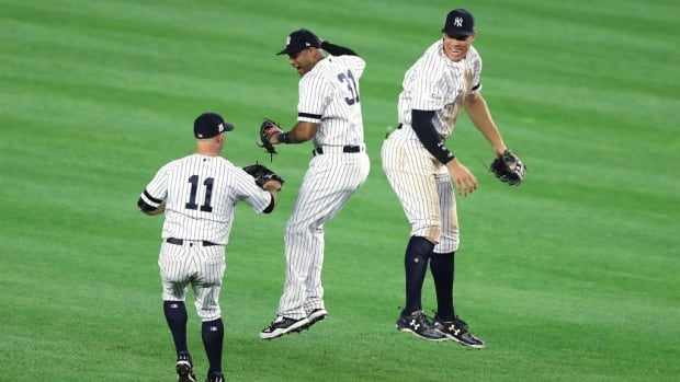 New York Yankees' Aaron Judge celebrates with Aaron Hicks and Brett Gardner after defeating the Minnesota Twins.