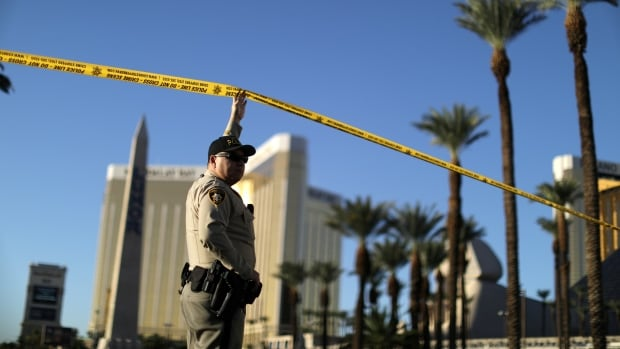A police officer stands in front of the closed Las Vegas Strip next to the site of the Route 91 Harvest music festival mass shooting on Tuesday. Investigators are still baffled about the motive of the gunman, Stephen Paddock.