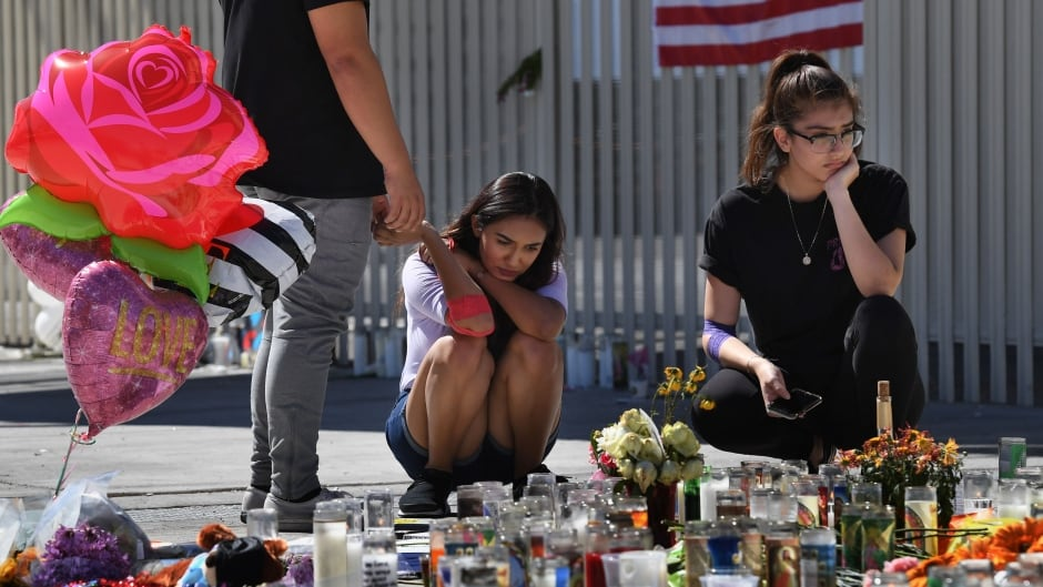 Briana Calderon, centre, and Cinthya Olbera pray at a makeshift memorial on the Las Vegas Strip on Oct. 3, after a gunman killed 59 people and wounded more than 500 others when he opened fire from the Mandalay Hotel on a country music festival.