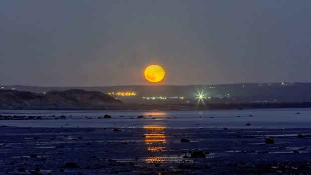 A spooky orange moon rises over McLarens Beach in west Saint John. The harvest moon this year will be at its peak Thursday.