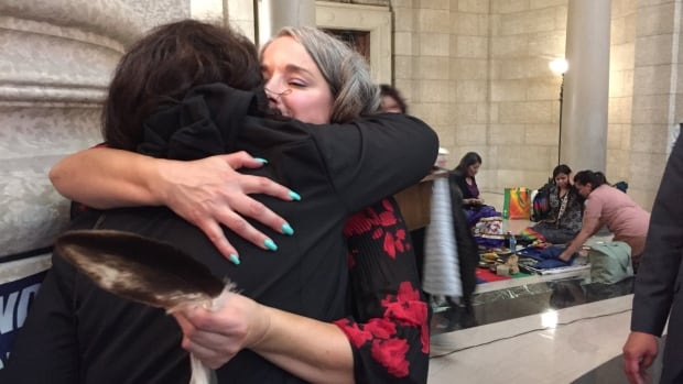 NDP MLA Nahanni Fontaine hugs one of the family members in attendance Wednesday at the Manitoba Legislature.