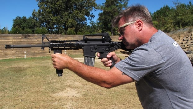 Shooting instructor Frankie McRae aims an AR-15 rifle fitted with a bump stock at his 37 PSR Gun Club in Bunnlevel, N.C. The device uses the recoil of the semi-automatic rifle to let the finger 'bump' the trigger, making it different from a fully automatic machine-gun, which is illegal for most civilians to own.