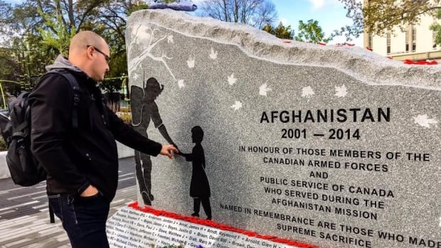 Lt. Michael McCauley takes a moment next to his likeness on the Greater Victoria Afghanistan Memorial featuring his silhouette and that of a young boy he shared a handshake with more than a decade ago.