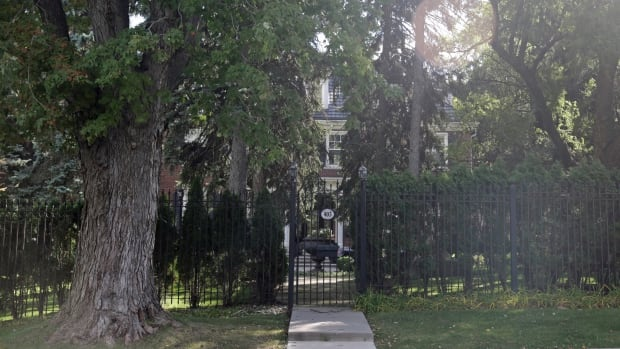 The property, 403 Queen Street South, is heavily wooded and encircled by a wrought iron gate.