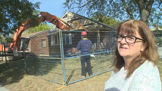 Long-time Sandwich Towne resident Caroline Taylor watches as the first home is torn down on Indian Road.