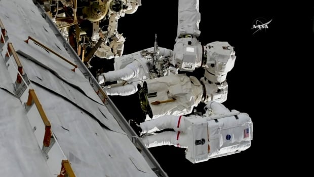 In this frame grab from NASA TV, Aastronauts Mark Vande Hei and Randy Bresnik, bottom, work on the International Space Station on Thursday to replace a part on Canada's robotic arm, the Canadarm2.