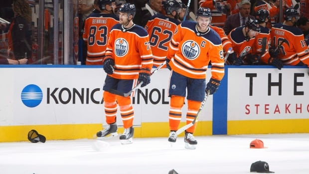 Connor McDavid smiles watching the hats rain down after his hat trick in Edmonton's season-opening win against the Flames.