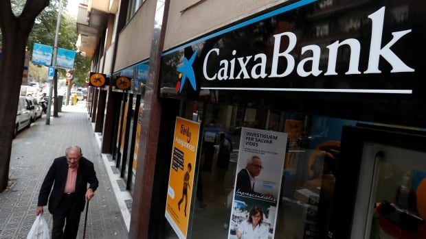 A man walks past a Caixa bank branch in Barcelona on Friday.
