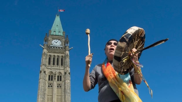 Chief Marcia Brown Martel sings outside Ottawa's Parliament buildings following a government news conference Friday announcing a compensation package for Indigenous victims of the Sixties Scoop.