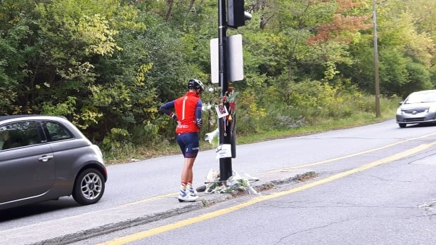 Philippe Tremblay stops at a makeshift memorial set up at the foot of Camillien-Houde Way for Clément Ouimet, the 18-year-old cyclist who died Wednesday when he struck an SUV that unexpectedly pulled a U-turn in front of him.