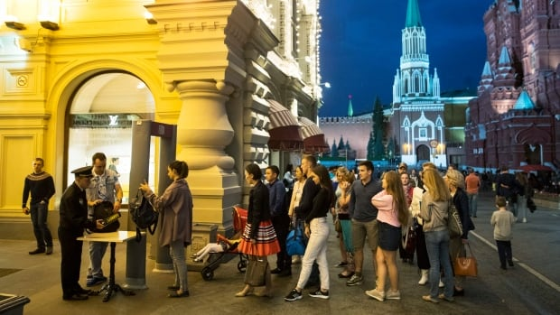 People are checked by security guards in September before entering the GUM department store at Red Square in Moscow.