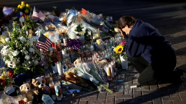 A woman pauses at a makeshift memorial in the middle of Las Vegas Boulevard on Friday for the victims of the mass shooting.