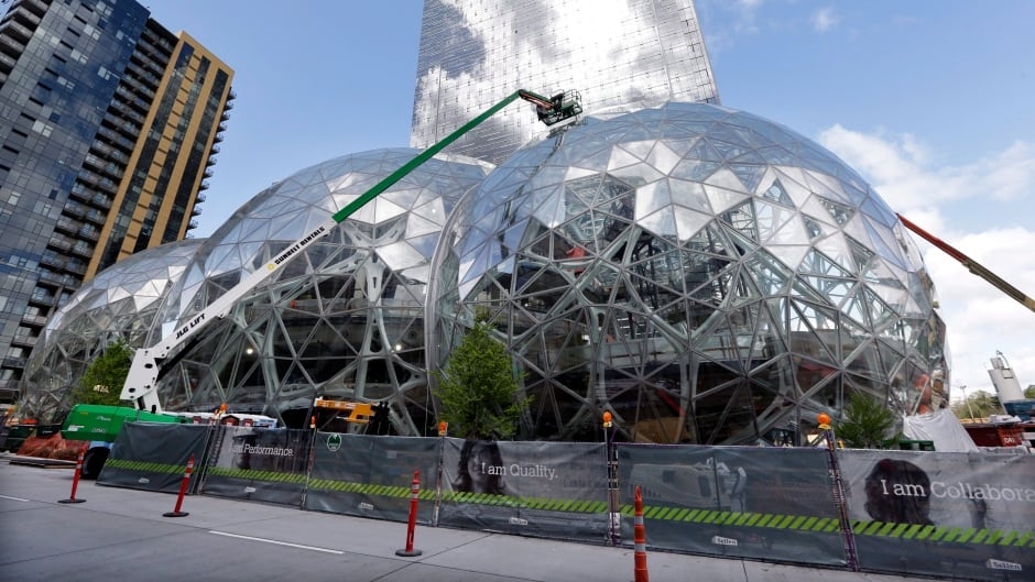FILE - In this April 27, 2017 file photo, construction continues on three large, glass-covered domes as part of an expansion of the Amazon.com campus in downtown Seattle. Amazon said it will spend more than $5 billion to build another headquarters in North America to house as many as 50,000 employees.