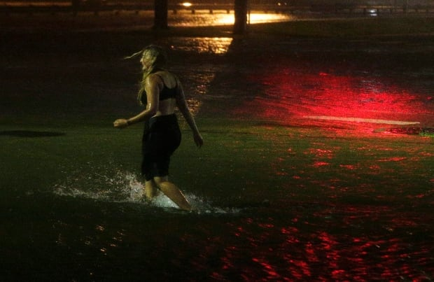 A woman wades through a flooded street in downtown Mobile, Ala., on Sunday. Hurricane Nate came ashore along Mississippi's coast outside Biloxi early Sunday, and was later downgraded to a tropical depression. (Brynn Anderson/Associated Press)