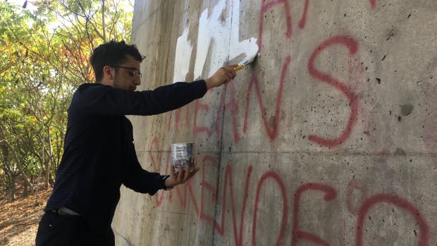 Ahmed Khalifa covers anti-Islamic messages with white paint Sunday afternoon.