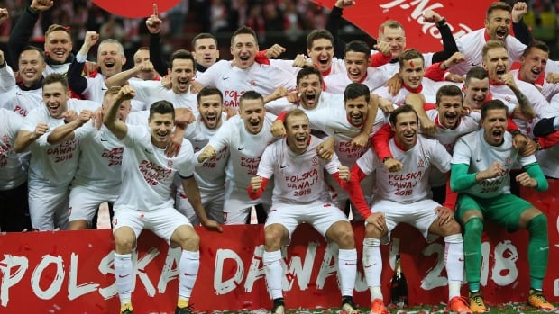 Poland players celebrate after winning their last World Cup Group E qualifying soccer match against Montenegro to qualify.
