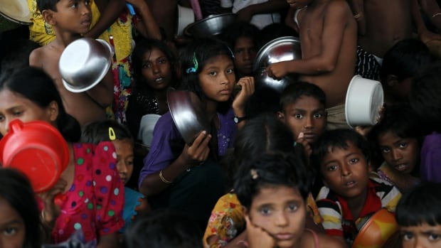 Rohingya refugee children wait for lunch at a refugee camp in Cox's Bazar, Bangladesh.