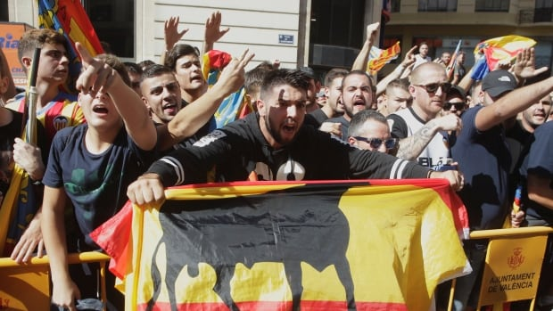 Right-wing demonstrators accuse leftist politicians of sympathizing with the Catalan separatist movement during the festivities of the regional day in Valencia, Spain.