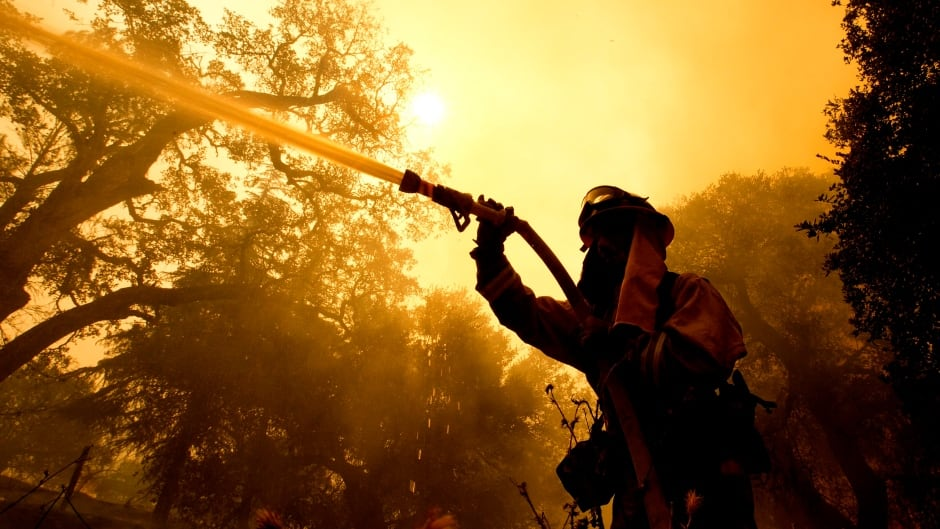 Napa County firefighter Jason Sheumann sprays water on a home as he battles flames from a wildfire Monday, Oct. 9, 2017, in Napa, Calif. More wastewater has been discharged into the Niagara River in the latest in a series of overflows since a discharge blackened water near Niagara Falls in view of summer tourists.