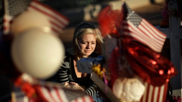 Alexandra Gurr cries Monday as she lays flowers at a makeshift memorial for victims of the Vegas mass shooting.