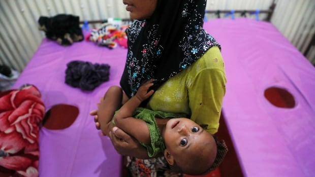 A woman holds her child at a dysentery clinic run by Medical Teams International at the Kutupalong Rohingya refugee camp near Cox's Bazar, Bangladesh on the weekend.