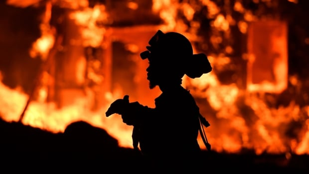 An inmate firefighter monitors flames as a house burns in the Napa wine region in California.