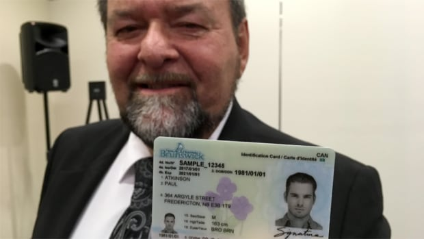 Justice and Public Safety Minister Denis Landry shows off an example of New Brunswick's new drivers licences.