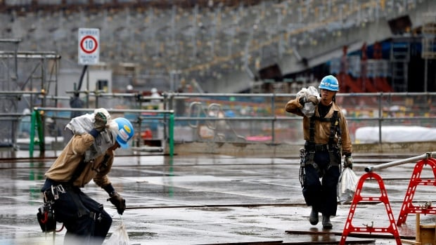 Labourers work at a construction site of the new national stadium in Tokyo in September. The Japan labour standard office has determined the suicide of a 23-year-old man who worked at Tokyo's new Olympic stadium construction site stemmed from overwork.